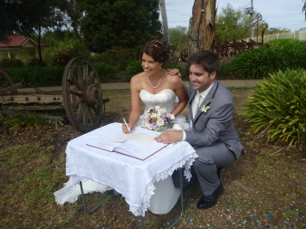 Erin Dellar and Brady Nicholls signing the register during their wedding at Emerald Bank on 7th March 2015